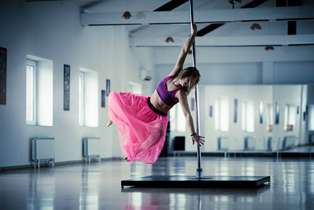 Dance performer dancing on a pole in a studio.